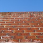 red brick wall and bright blue sky
